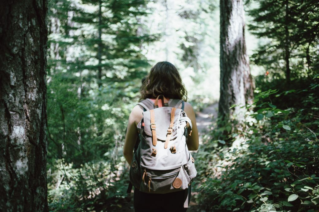 jeune femme avec sac à dos en randonnée dans la forêt