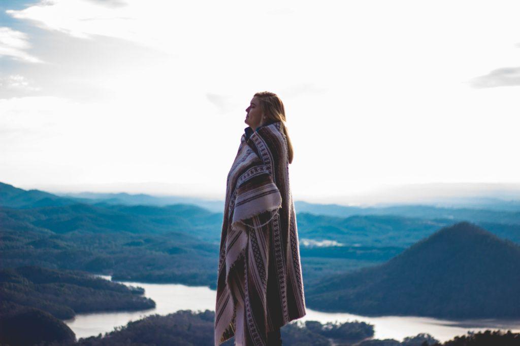 jeune femme entourée d'un plaid regardant le paysage montagneux